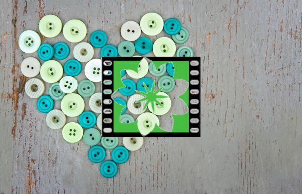 Green buttons in shape of a heart on wooden vintage background
