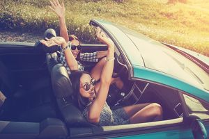 Two attractive young women in a convertible car