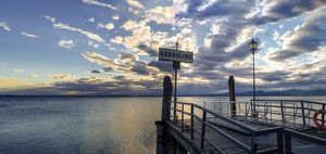 Sunset over pier at lake Garda in Bardolino Italy. Panoramic view on sunset over pier